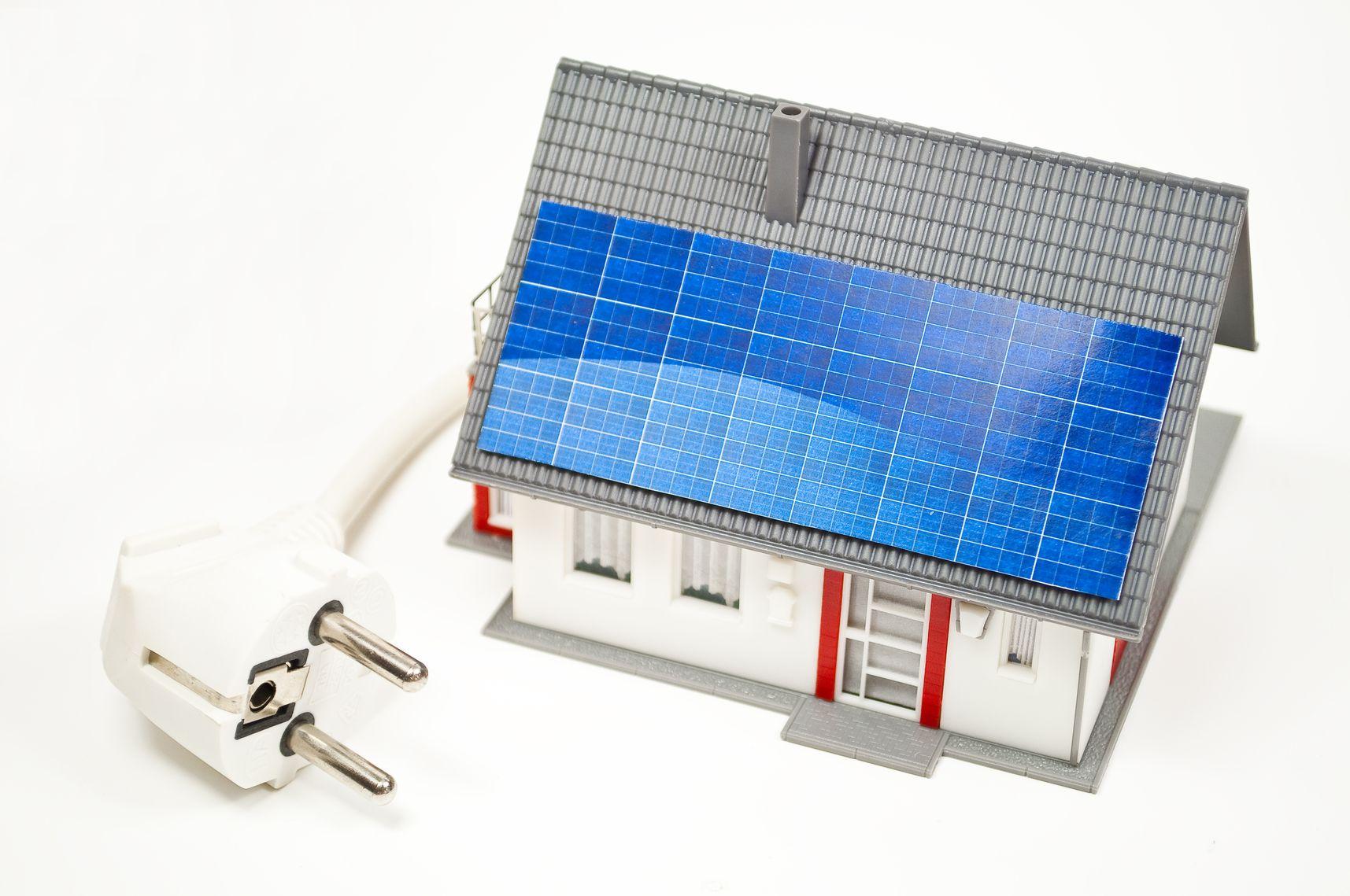 Haus mit Solarzellen und Stecker